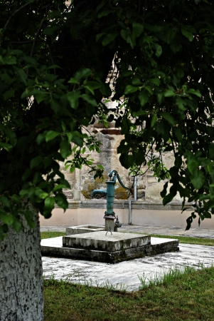 Hand water pump in the churchyard on a concrete pedestal in the shade of a tree. photo