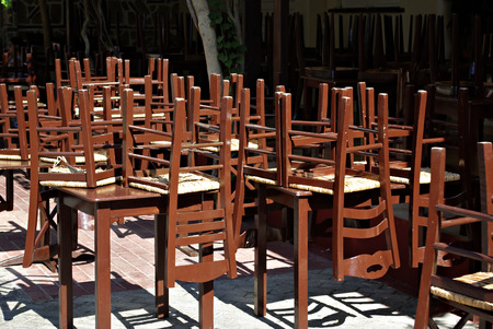 Closed restaurant with old fashioned brown wooden chairs set upside down on tables at sunny summer day.