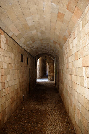 Empty stone passage inside old medieval fortress lit by sun at end. photo
