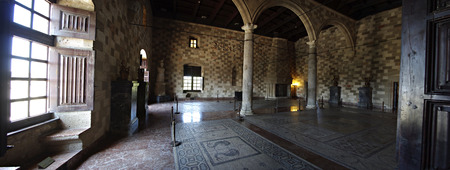 Big room with fire place, mosaics, columns and arcs inside medieval castle.