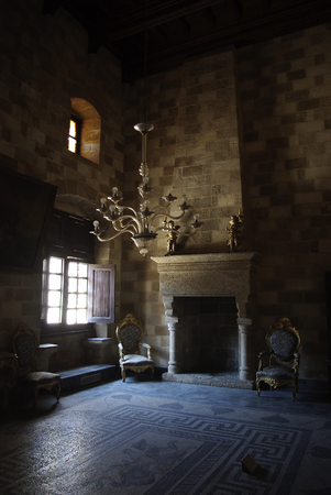 Stone fireplace and armchairs at old medieval castle.