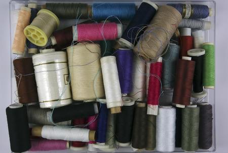 Sewing cotton in different colors, packed and unpacked, in plastic box. photo