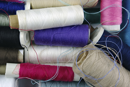 unpacked: Sewing cotton in different colors, packed and unpacked, in plastic box. Stock Photo