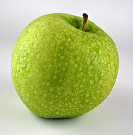 Organically grown fresh juicy green apple isolated on white background.