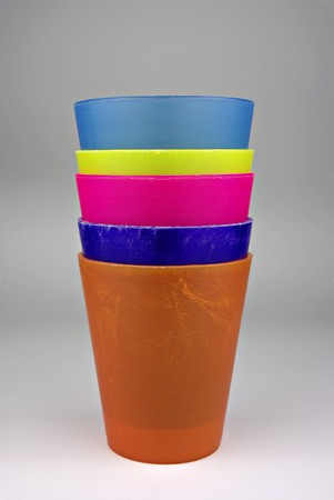 Colorful plastic glasses, stacked and ready for use. Stock Photo