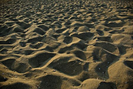 Sandy beach with foot tracks and hard shadows at suny summer afternoon.