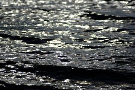 Sea surface with out of focus sun reflections and waves at sunny summer afternoon.