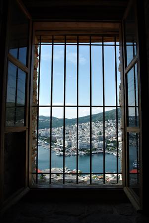 City panorama through window bars, white buildings and blue sky. Stock Photo