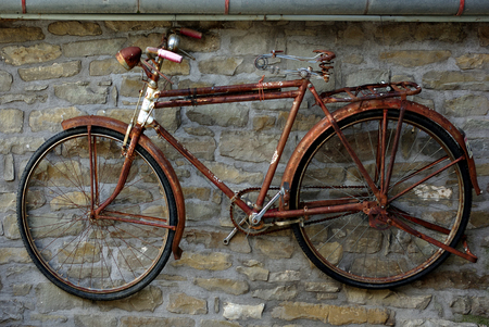 Old rusty bicycle hanging on stone wall.