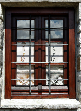 Wooden window with elegant curtains, sky reflection and steel bars on the stone house.