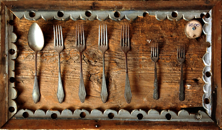 Old forks and spoon with wooden frame and price tag.