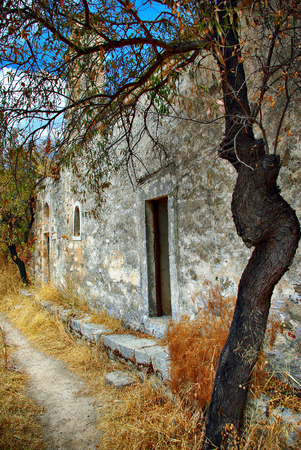 Old stone house in dry grass at sunny sunner day. Stock Photo
