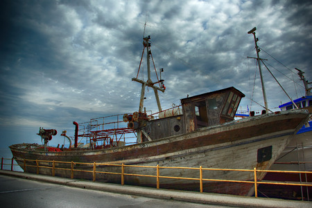 Abandoned old fishing wooden boat at seaside at sunny cloudy day. Stock Photo