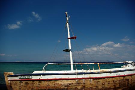 Abandoned fishing wooden rowboat at seaside at sunny summer day.
