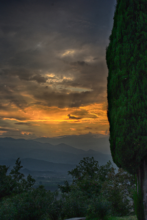Sunset at mountain, hills in background, cloudy sky, woods in front. Stock Photo