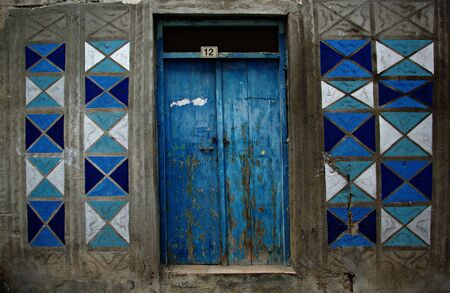 Blue entrance door with blue shaded square ornaments.