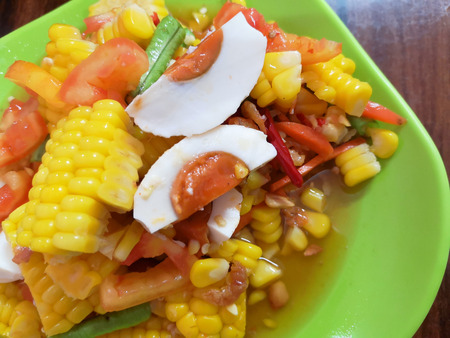 som tum or papaya salad or corn salad is a traditional spicy thai food cooked with carot salted egg and chilli