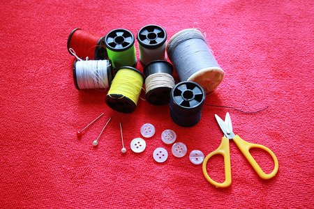 old spools: Spools of thread with needles on red background. Old sewing accessories. colored threads Stock Photo