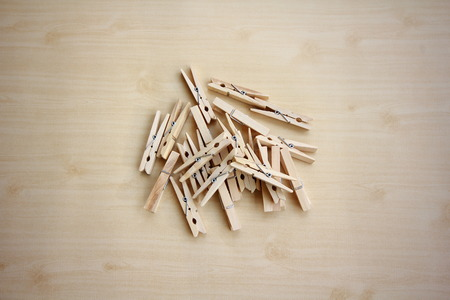 undies: wooden clothespins piled on the floor and dark wood.