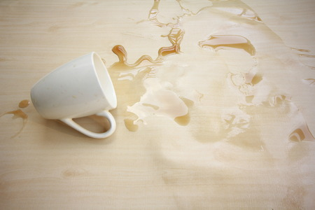 te negro: Day break? Stress getting to you? Black coffee spilled on the wooden floor. Foto de archivo