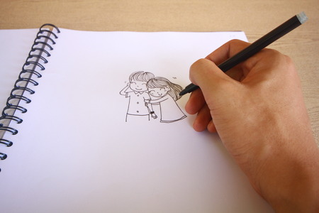 pencil and paper: cartoon drawing notebook on wooden desk background.