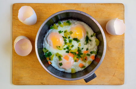 Fried eggs in a frying pan on wooden cutting board