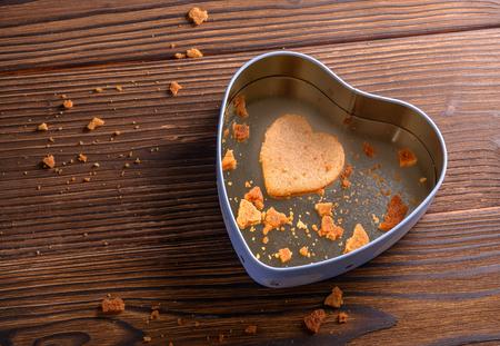 galleta de jengibre: Sola galleta de jengibre hecho en casa en la caja en forma de corazón sobre fondo de madera Foto de archivo