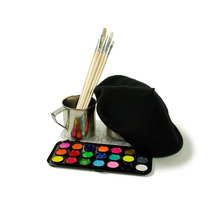 Colorful paints used for various projects, Paint brushes used for many different mediums, Black Beret that wears tight to the head, Stainless steel cup for drinking or holding items Banco de Imagens