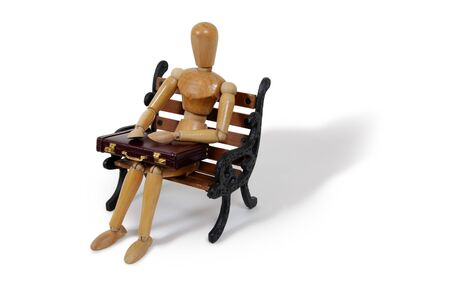Wooden model representing a person sitting on bench with  leather Briefcase used to carry items to the office Stock Photo - 3953901