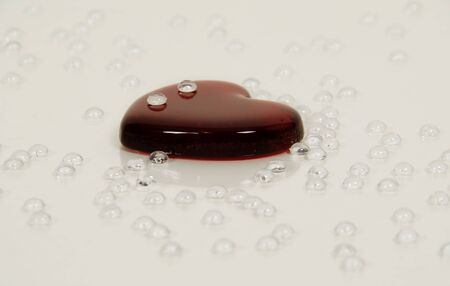 tearful: Tear drops of wet liquid on red glass heart