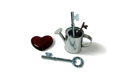 jailer: Small metal watering can for bringing life to the plants, Metal Heart basket with intricate patterns, Keys representing unlocking an idea, treasure, or love Stock Photo
