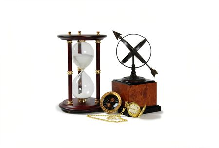 Gold pocket watch with a metal chain, Antique time zone converter used by travellers, Sundial telling the number of hours to go or the years left, Hour glass used to measure time photo