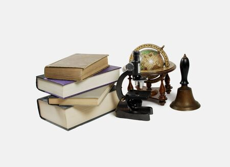 old items: Small Microscope used in sceientific research Large book  Old world globe with basic navigation notations Antique School bell with wooden handle and brass clapper A variety of teaching and student items