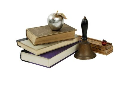 old items: Silver apple with a silver metal leaf texture, Antique School bell with wooden handle and brass clapper, Creative pencil box made up of rulers and wooden apple, Large books Stock Photo