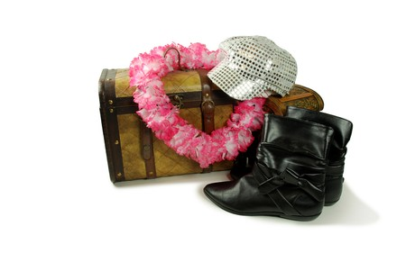 A pair of old cases for storing items, Pink and white Lei representing vacations and free time, Cap with brim with sparkle dots that reflect, Black leather boots to be worn on the feet