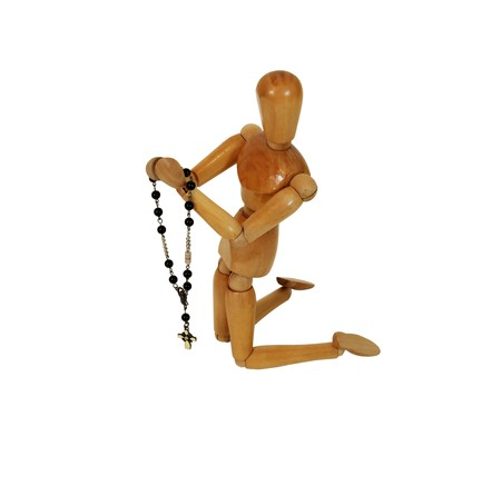 catholism: Rosary beads used for prayer in the Catholic faith, hands held together in prayer during many religious ceremonies, Wooden model representing a person Stock Photo