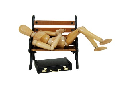 Leather briefcase used to carry items to the office, wooden park bench with metal scroll sides, wooden model representing a person
