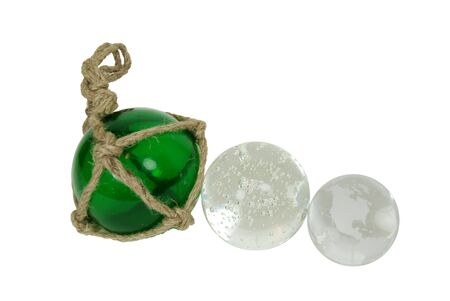 minature: Green nautical glass float tied with rough rope, crystal ball for seeing into the future with miniature bubbles inside, Crystal globe with navigational lines Stock Photo