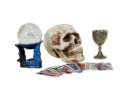 Skull with eye sockets and teeth, crystal ball for seeing into the future with miniature bubbles inside, silver antique chalice with grapes and leaves embossed on the sides