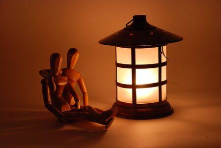 brighten: Sitting in front of a bright lantern on a dark night