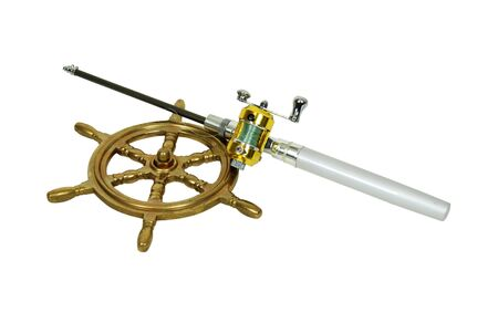 brass rod: Fishing pole with rod and reel used to catch fish, nautical steering wheel made of brass Stock Photo