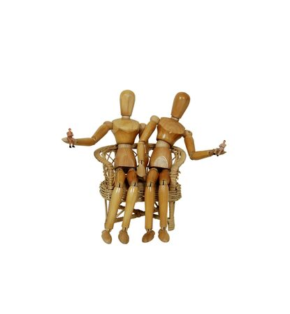 Wooden models sitting in a chair holding small people representing inspiration, ideas and muses Stok Fotoğraf