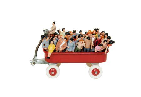 brings: Una variet� di persone raggruppate per rappresentare la diversit� in un piccolo carro rosso riporta ricordi di infanzia Archivio Fotografico