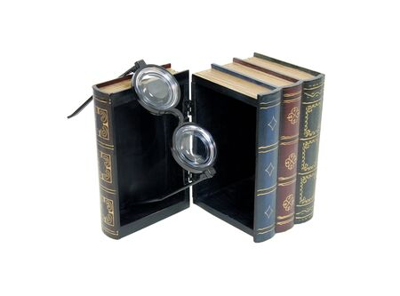 resemble: Large wooden block hollowed and carved to resemble a book with black horn rimmed glasses hanging from the edge