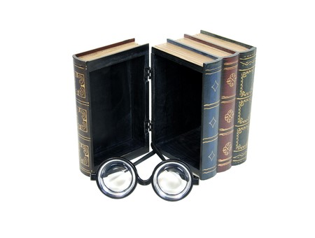 Large wooden block hollowed and carved to resemble a book with a pair of thick glasses Imagens