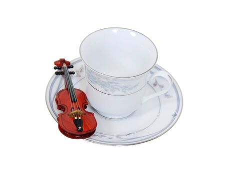 Formal tea cup with a delicate china pattern for drinking tea served with a violin on the side-Path orig size Stock Photo - 4490937