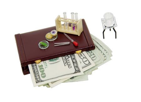 Scientific research items including bunsen burner, test tubes, and petri dish on a briefcase full of money-path orig size