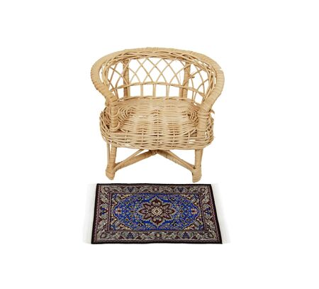 Informal wicker chair for sitting on the porch with a fancy rug at the foot