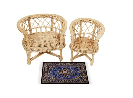 Woven love seat and chair in front of an intricate rug