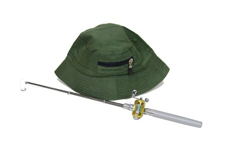 Fishing pole with rod and reel used to catch fish and a hat to avoid sunburn